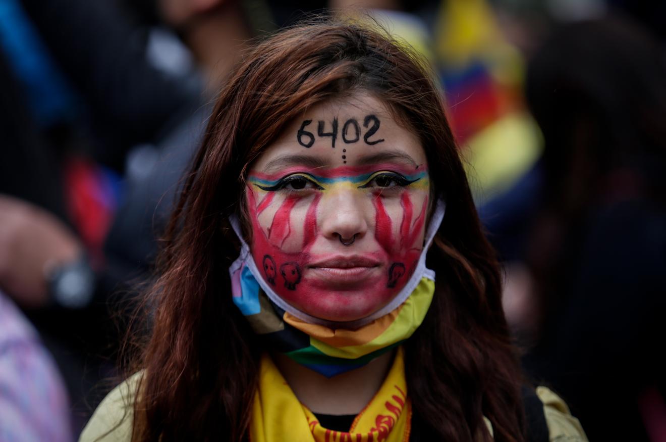 """Una joven participa en una protesta contra el gobierno el Día de la Independencia de Colombia. En su frente tiene el número """"6402"""" en alusión a los civiles asesinados por los militares. Foto: Mariano Vimos / colprensa / dpa"""