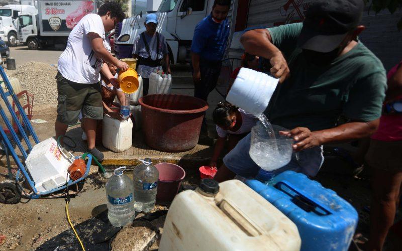 Acapulco, Gro/22Septiembre2021/ Comerciantes del Mercado Central y vecinos del barrio de La Fabrica llenan  cubetas y  botes de agua de una  fuga que brota   abajo del concreto frente la subestación de Bomberos en la avenida 16 de Septiembre y Constituyentes en Acapulco. Foto: Jesús Trigo